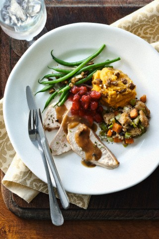 Holiday dinner plate with turkey breast, gravy, stuffing, sweet potato, green beans and cranberries on tabletop